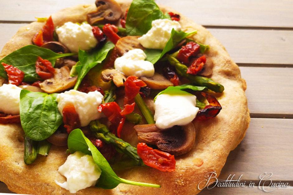 Pizza con pomodori secchi, spinaci, asparagi e spuma di burrata